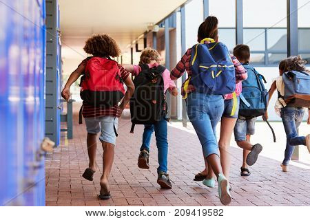 School kids running in elementary school hallway, back view