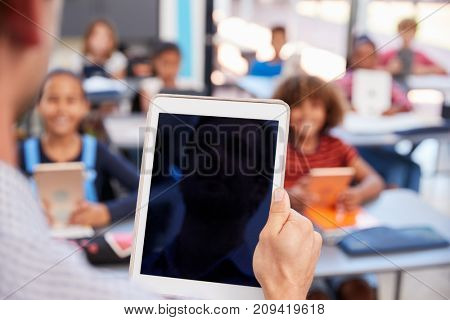 Teacher holding tablet in school class, over shoulder view