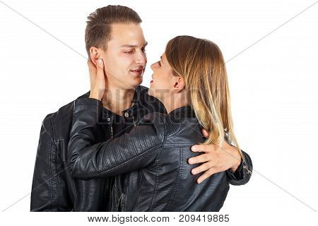 Young romantic couple wearing black leather jackets cuddling on isolated background
