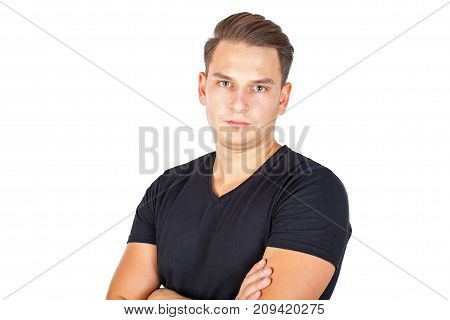 Confident young man looking at the camera on isolated background with arms crossed