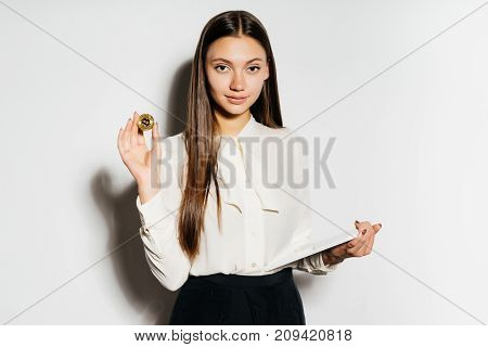 a young confident business lady is studying crypto currency, is holding a gold bitcoin and a tablet in her hand