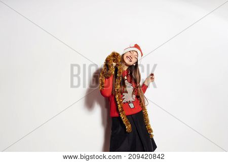 young happy cheerful girl celebrates New Year and Christmas, in a festive sweater and gold tinsel on the neck