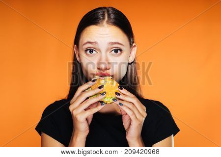 a young girl wanted to lose weight, but is eating a harmful hamburger