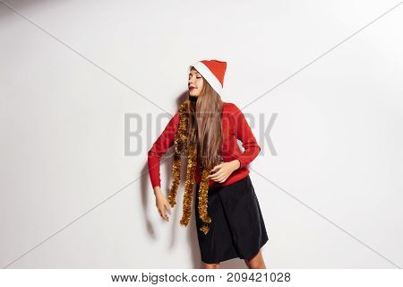 beautiful girl celebrates the new year in the festive cap of Santa Claus, and the golden tinsel