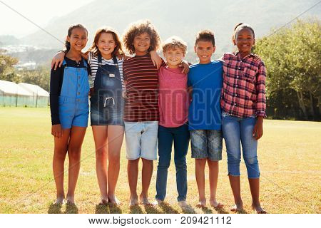 Full length portrait of six pre-teen friends in a park