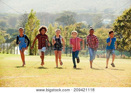 Six pre-teen friends running in a park, front view