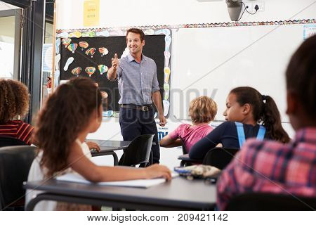 Teacher gesturing to class in an elementary school lesson