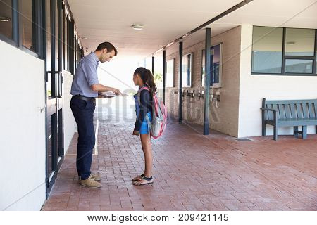 School teacher showing book to schoolgirl outside classroom
