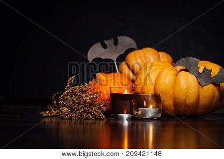 composition for decorating a house for halloween, yellow and orange pumpkins, burning candles, drawings of black bats