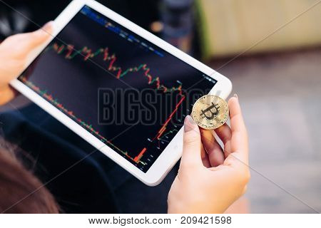 the girl holds a tablet in her hands and looks at the graphics, as well as the golden bitcoin