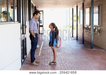 School teacher talking with schoolgirl outside classroom