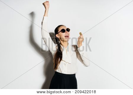 happy business woman in sunglasses laughs and holds in her hand a gold bitcoin, a crypto currency