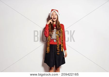 a young enthusiastic girl is happy with the new year and Christmas, and laughs with a golden tinsel on her neck