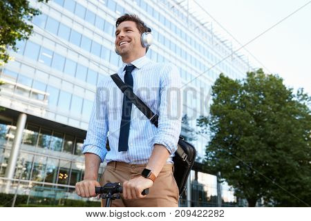 Businessman Wearing Headphones Commuting To Work On Scooter