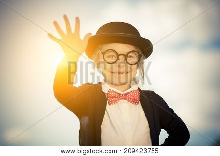 Outdoor portrait of funny little girl in bow tie and bowler hat with hello gesture. Retro stile.