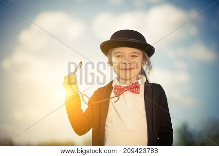 Outdoor portrait of funny little girl in bow tie and bowler hat holding glasses. Retro stile.