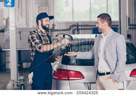 Deal! Side Profile Shot Of Cheerful Professional Repairman In Cap And Uniform, Presenting Keys Of Si