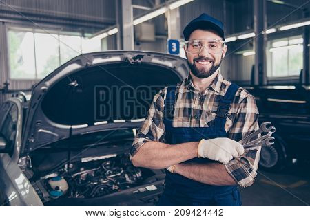 Attractive Caucasian Brunet Bearded Expert Mechanic Standing With Metal Mechanical Keys In Arm, In S