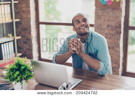 Young Dreaming Mulatto American Worker Is Thinking In Front Of Laptop At Work Place. He Is Happy, Sm
