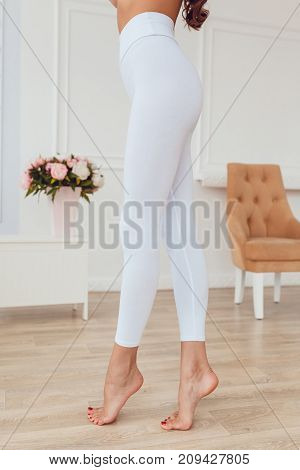 Legs of a sexy girl in white leggings. Mock-up.