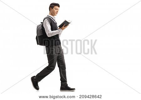 Full length profile shot of a teenage student reading a book and walking isolated on white background