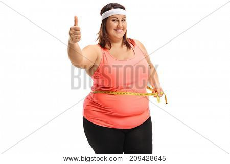 Overweight woman measuring her waist with a measuring tape and making a thumb up sign isolated on white background