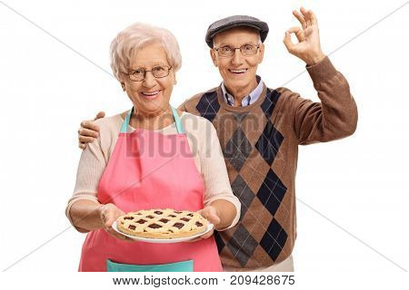 Elderly woman holding a freshly baked pie and an elderly man making an ok sign isolated on white background