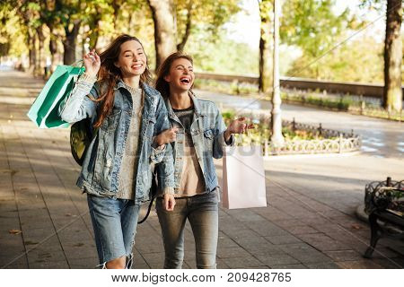 Portrait of two cheery young girls holding shopping bags and pointing while walking on a city street