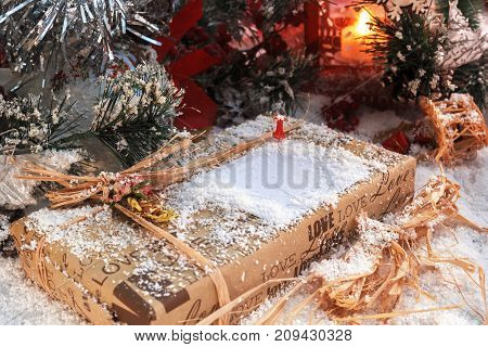 Christmas present with place for text covered with snow in the light of a red lantern on the background of New Year's scenery