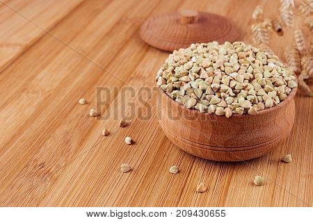 Green buckwheat in wooden bowl on brown bamboo board close up. Rustic style healthy dietary groats background.