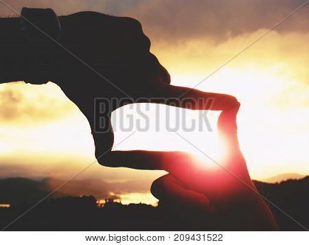 Close Up Of Hands With Watch Making Frame Gesture. Dark Misty Valley Bellow In Landscape.