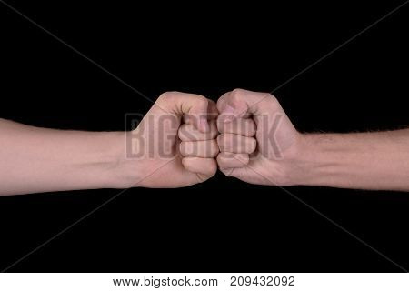 The image close-up of the collision of two fists on a black background. The concept of confrontation competition or friendship