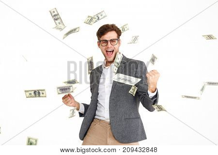 Portrait of happy cheerful man in eyeglasses and a jacket standing and celebrating success with falling money banknotes isolated over white background
