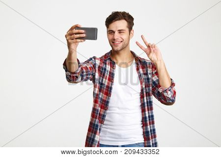Portrait of a smiling attractive man taking a selfie while standing and showing peace gesture isolated over white background