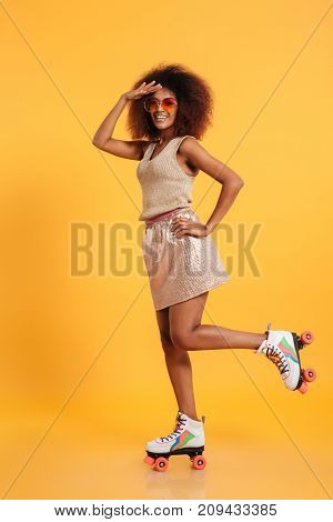 Full length portrait of a happy afro american woman dressed in retro clothes and wearing skates while standing and looking far away with hand at her forehead isolated over yellow background