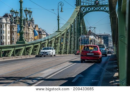 Budapest, Hungary - August 14, 2017:  Liberty Bridge in Budapest. Traffic crossing the bridge. It connects Buda and Pest across the River Danube. Sunny day of summer