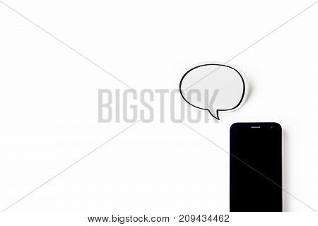 Business concept - Top view of modern office desktop background with blank bubble sticker and smart phone for mockup design and copy space isolated on white background
