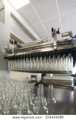 A lot of glass bottles hanging in the pneumatic gripper. Automatic pallet unloading machine.