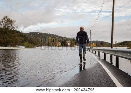 Man walking in the water on the flooded road. Flooding from the river Tovdalselva in Drangsholt in Kristiansand, Norway - October 3, 2017.