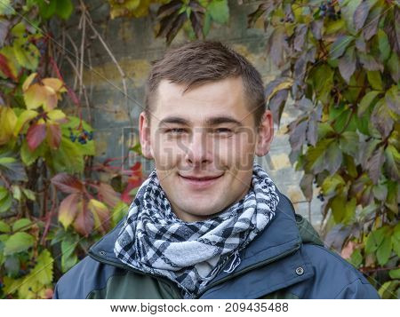 Portrait of a cute young guy on a walk in an autumn park against a background of yellowing leaves