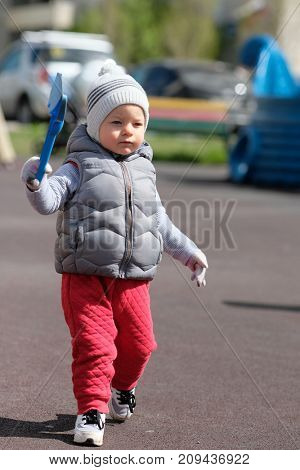 Portrait of toddler child in warm vest jacket outdoors. One year old baby boy wearing vest jacket at playground