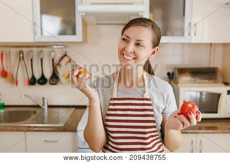 A Young Attractive Happy Woman In An Apron Decides To Choose A Red Or Yellow Tomato In The Kitchen.