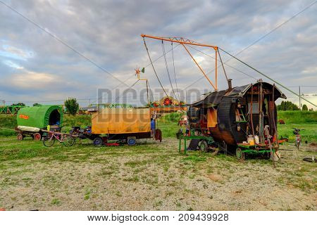 Three horse-drawn wagons and an aerial rig are set up for a circus performance.