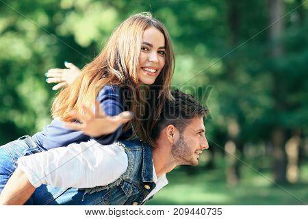 Happy Young Girl On Back Of Guy Portraying Bird