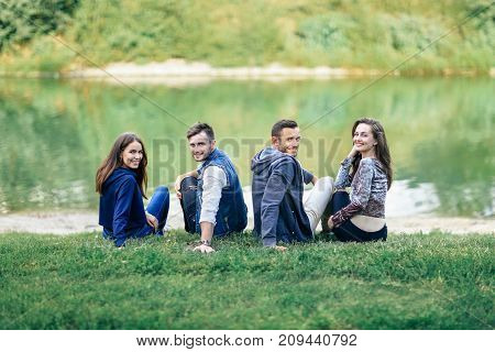 Two Couples Sitting On Grass By River Turned Looking Camera