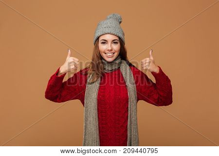 Smiling young woman in winter clothes showing thumbs up gesture with two hands, looking at camera, isolated on beige background