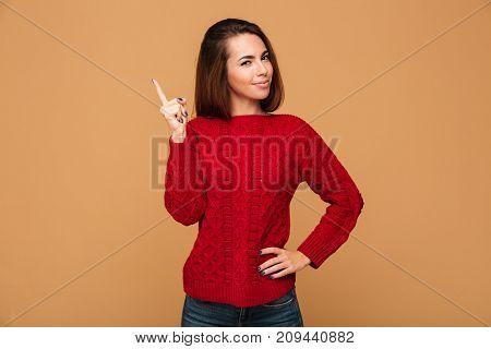 Close-up photo of charming brunette woman in red knitted sweater pointing with finger, looking at camera, isolated on beige background