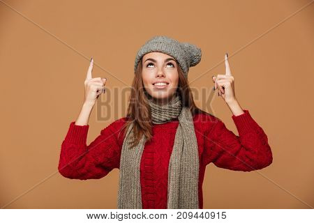 Smiling woman in winter clothes pointing with finger and looking upward, isolated on beige background