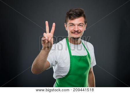 Portrait Of Attractive Male Supermarket Employer Showing Peace Gesture