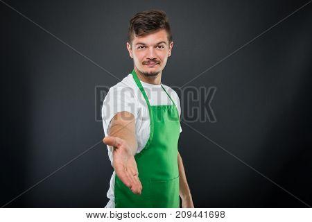 Portrait Of Attractive Supermarket Employer Offering Hand Shake